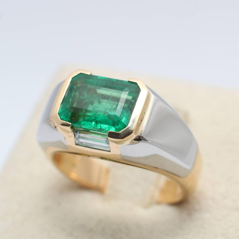 An Emerald and Diamond engagement ring. The richly coloured emerald (likely Columbia), 2,31 ct, is flanked by two baguette cut diamonds 0.40 ct in total E-F color, VVS clarity, all set in a white and yellow gold. Weight 7.9 gr. Ring size: US 6.