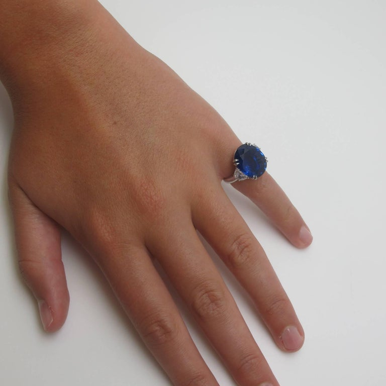 This platinum ring features a gorgeous royal blue color sapphire (12.23cts) set with 2 half-moon shaped diamonds that weigh a total of 1.50cts. The diamonds are fine quality;   VVS-2 clarity and D-E color.   The sapphire is accompanied by both AGL