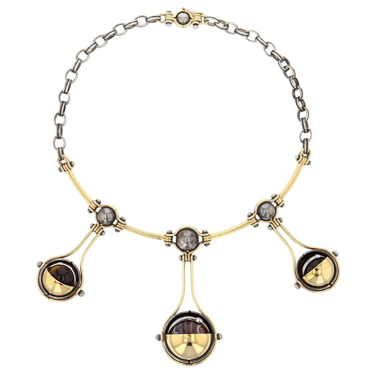 Elie Top 3 Drops Necklace Gold and Diamonds  Choker comprising a yellow gold articulated torc and a patinated silver chain. The three drops are made of two yellow gold threads around a patinated silver globe supporting a mobile structure. This in