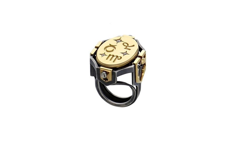 Bague Sceau Terre Or Onyx Diamants  Ring rail in patinated silver, adorned with gold coats of arms, pierced with motifs representing the seasons on the large ones and tarot colours on the smaller ones. The pivoting central medallion is in gold