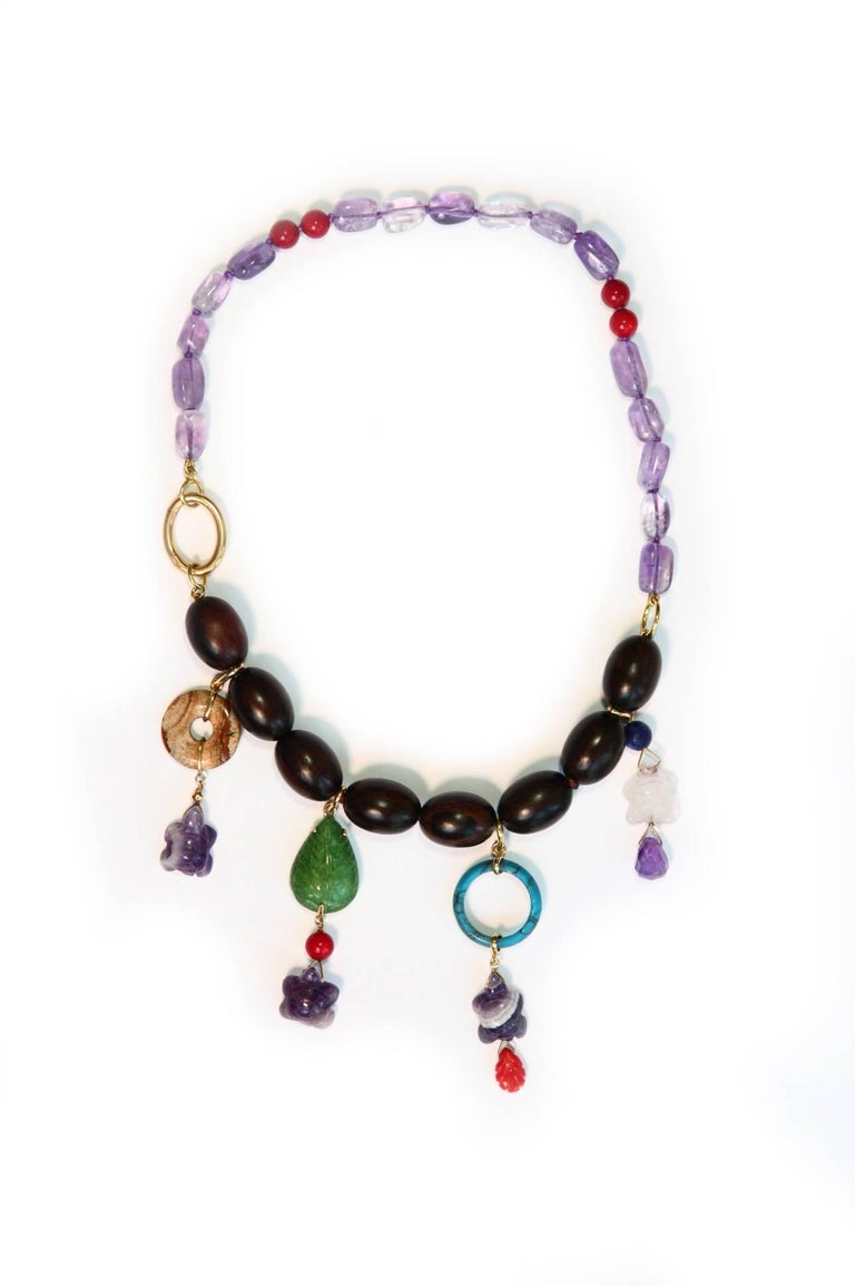 Necklace with ebony olives beads charms with different stone as emerald, turquoise, little coral leafs, jasper BI, amethyst stone, coral and 18kt gold gr.12,50. Total length is 45 cm weight 60,8 gr. All Giulia Colussi jewelry is new and has never