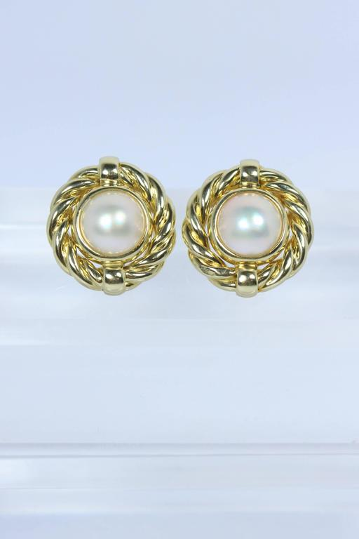 These earrings are composed of 18KT yellow gold with Mabe Pearl. There is a post backing with clip. In excellent vintage condition.