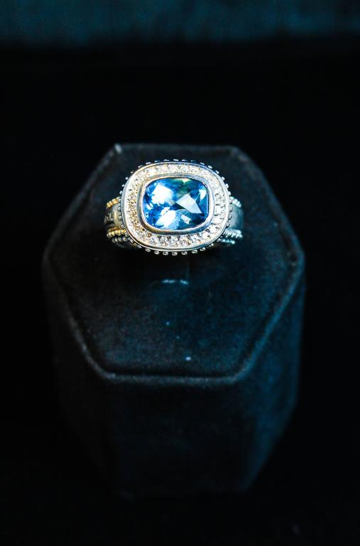 This beautiful ring features a stunning blue Topaz center stone and is composed of 18kt white gold. There are pave diamond accents. Specs below. In excellent condition.  Please feel free to ask any questions you may have, we are happy to assist.