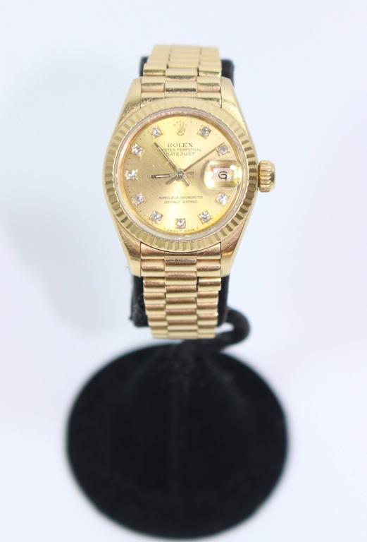 This fabulous Rolex  watch presented by The Paper Bag Princess of Beverly Hills features; Automatic winding, 29 jewels, Quickset date, sapphire crystal. 18k yellow gold case with fluted bezel (26mm diameter). Champagne dial with factory diamond hour