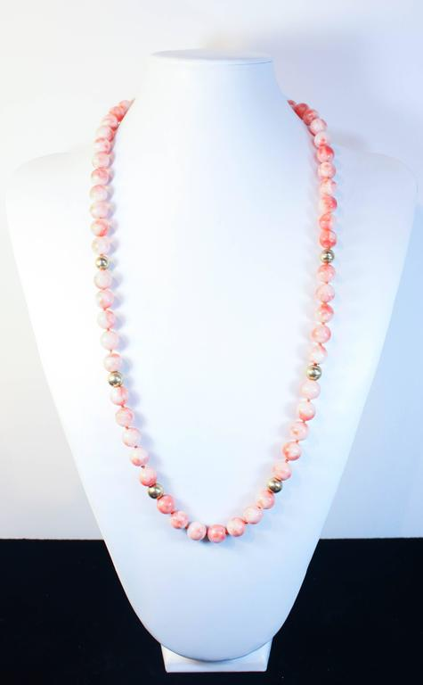 This necklace is composed of light coral beads with an approximate 11mm size. Features gold bead accents. In excellent condition.  Please feel free to ask any questions you may have, we are happy to assist.   Specs: 14KT Yellow Gold Beads Coral