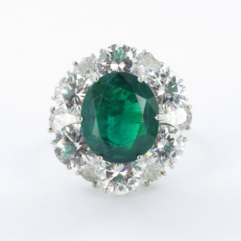 Emerald and diamond ring. Set with an oval shape Colombian emerald with a weight of approximately 5.50 carats, encircled by six brilliant cut diamonds, total weight approximately 4.70 carats (G/H colour and vs clarity) and six pear shape diamonds,