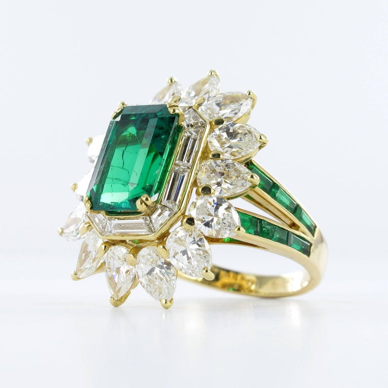 Colombian emerald and diamond ring by Mauboussin. Set with an octagonal step-cut emerald with an approximate weight of 3.30 carats, encircled by a single row of ten baguette cut diamonds in a bezel setting and further set with fourteen pear shape