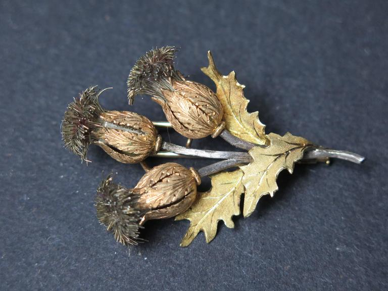 """An exquisite triple thistle brooch by Mario Buccellati. The thistle heads crafted of textured rose gold, with silver wire thistles on textured silver stems, with 18k yellow gold leaves. Signed M. Buccellati and 750 for 18K gold.  2.25"""" high,"""