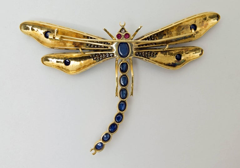 A large and beautifully hand made dragonfly brooch in 18K yellow gold with  applied enamel, 13 bezel-set cabochon sapphires, 117 bead-set round brilliant-cut diamonds and 2  bezel-set ruby cabochon eyes.  Diamonds weight:  1.20 carats, sapphires