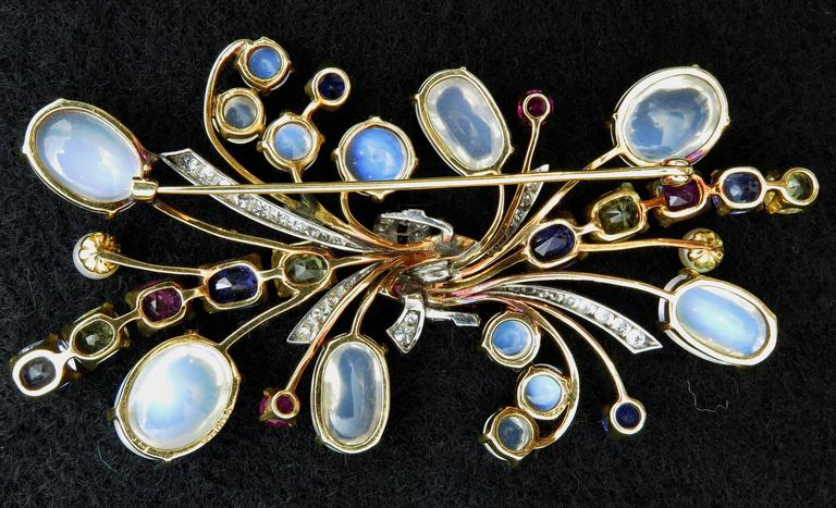 A large and beautiful hand crafted yellow and white 14K gold brooch with total approximately 45 carats of moonstones, 14 carats of sapphires, 1.04 carats of rubies, 1.1 carats of diamonds and 2 culture pearls.  The moonstones are transparent white