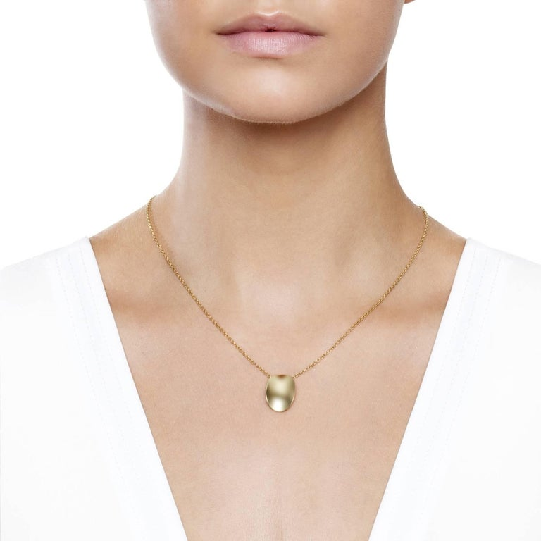 Yellow Gold Sculptural Oval Pendant Necklace in a pure simple graphic convex form allowing the play of light on the polished surface. The Ellipse design featuring a perfectly balanced concave form that plays with reflections of light from its high