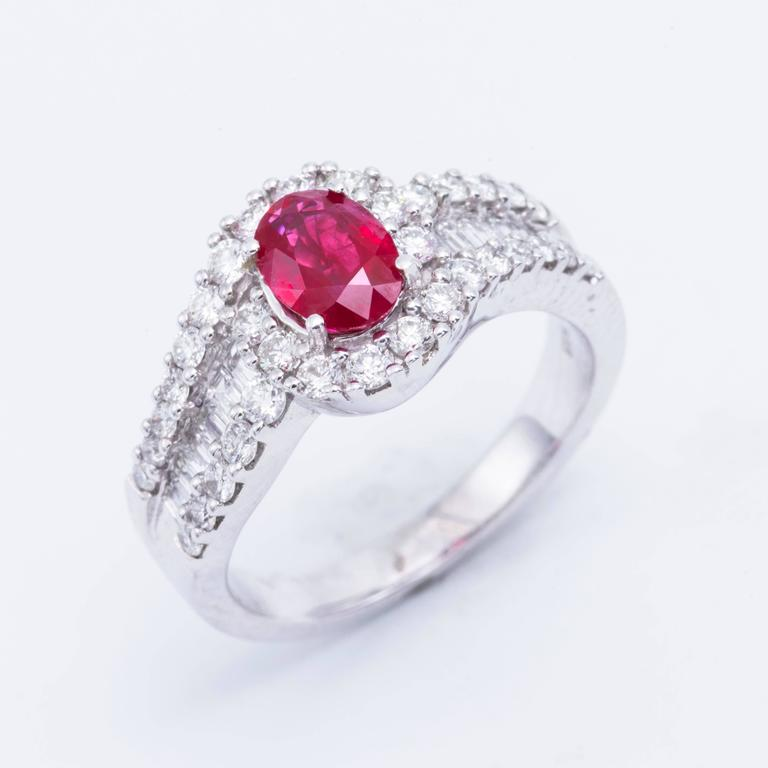 Style: 14k White Gold  Oval Shape Ruby  Diamond Halo Engagement Ring Material: 14k White Gold Gemstone Details: 1 Oval Shape Ruby approximately 1.88 ct.  Diamond Details: Approximately 0.47ctw of diamonds. Diamonds are H in color and SI in