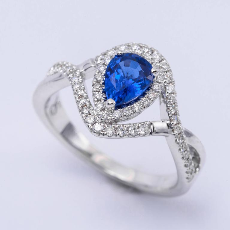 Style: 14k White Pear Shape Sapphire Diamond Halo Engagement Ring Material: 14k White Gold Gemstone Details: 1 Pear Shape Sapphire approximately 0.93 ct. 7x5 mm Diamond Details: Approximately 0.33 ctw of diamonds. Diamonds are H in color and SI in