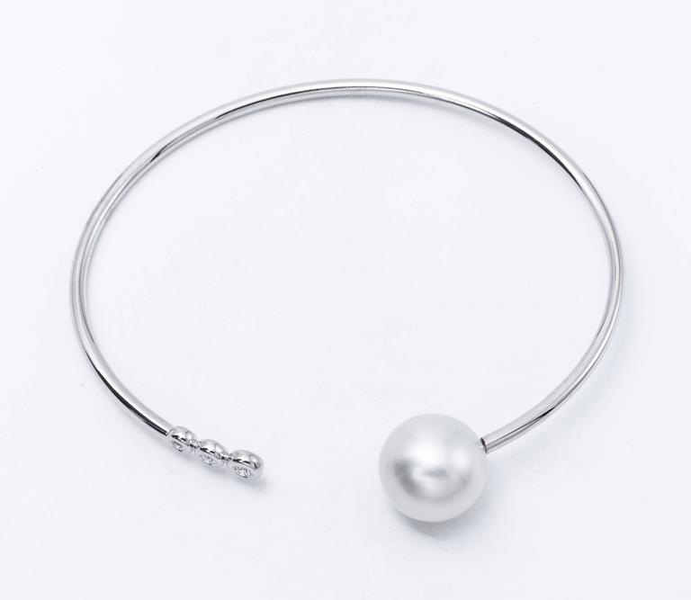 18K White gold open bracelet featuring one South Sea Pearl measuring 11-12 mm and three diamonds weighing 0.10 Carats. Color G-H Clarity SI  Pearls can be changed to Pink, Tahitian or Golden upon request. Price subject to change.