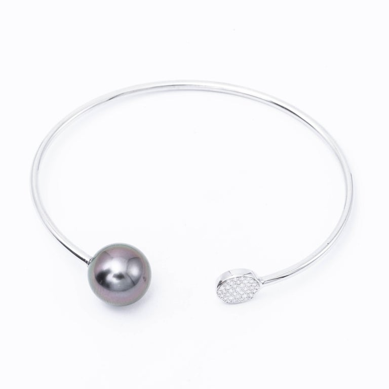 18 Karat white gold bangle bracelet featuring 32 round brilliants weighing 0.12 carats and one grey Tahitian Cultured Pearl measuring 11-12 mm. Color G-H Clarity SI