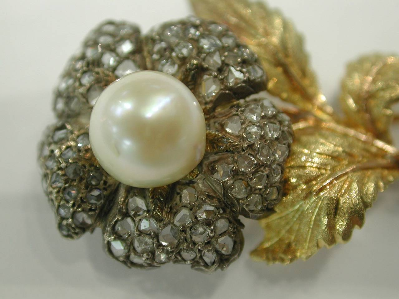 A sophisticated ,classic brooch crafted by Buccellati, featuring Rose Cut Diamonds and Cultured Pearls on a 18k yellow gold mounting. Approximately 80 diamonds 0.60Cts. Metal:8.8 grams