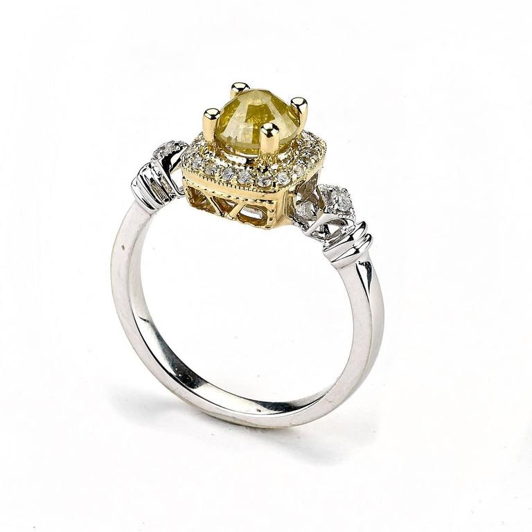 This Ring features a Fancy Yellow Diamond Surrounded by White Diamond Accent and Lays in two Tone Yellow and White Setting.