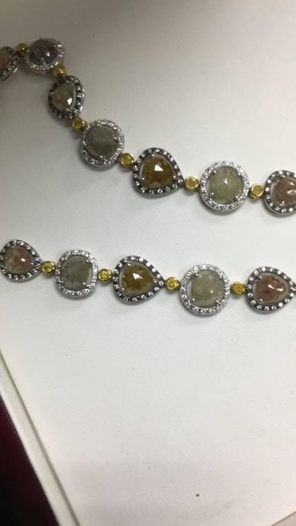 This spectacular one of a kind Y shaped necklace features 24 Pear Shaped Rough Fancy Diamonds for a total weight of 55 Cts in different shades of green and some grey in the back with a greenish overtone to them. The Necklace contains 436 White
