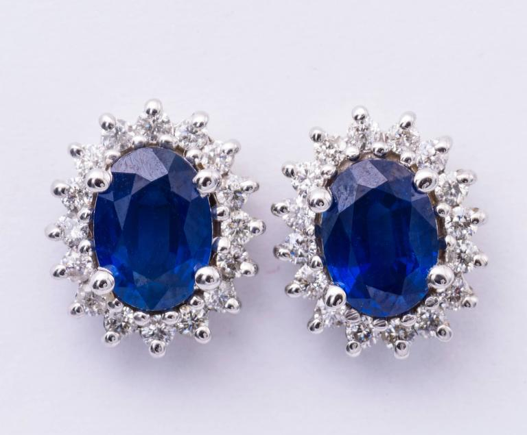 These sapphire earrings are available in white gold. The center stone may be special-ordered in any precious gemstone color. The oval sapphire in these earrings have a total carat weight of 1.88 carats, and they measure 7x5 MM.. The diamonds have a