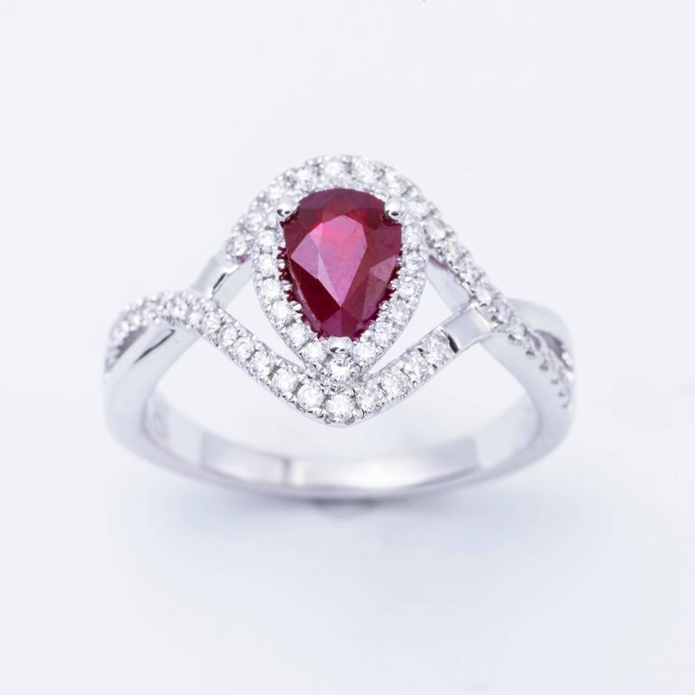 Style: 14k White Pear Shape Ruby Diamond Halo Engagement Ring Material: 14k White Gold Gemstone Details: 1 Pear Shape Ruby approximately 0.92 ct. 7x5 mm Diamond Details: Approximately 0.33 ctw of diamonds. Diamonds are H in color and SI in