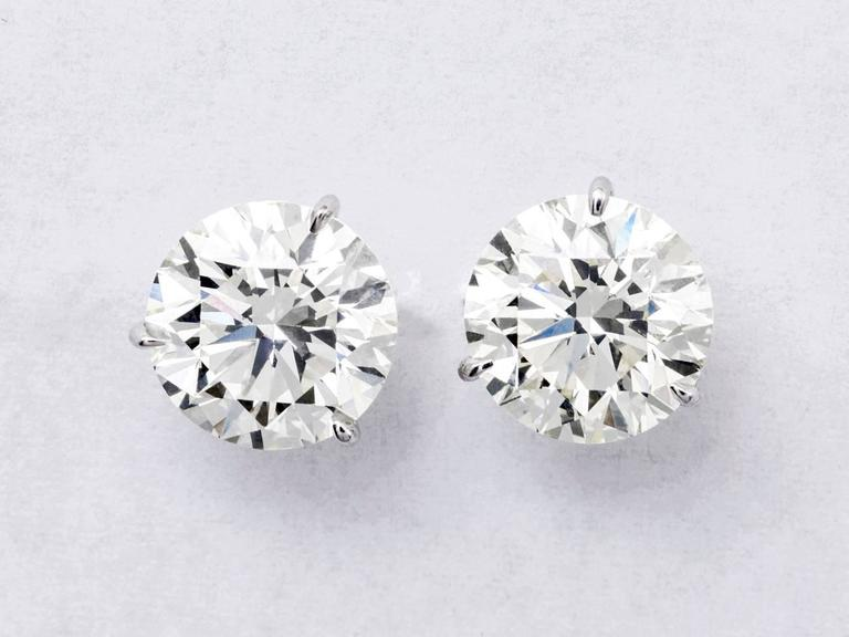 This Studs Features: 7.16T/W Metal: 18k Gold: White Gold Color: K-L Clarity: VS2 3 Prong, Champagne Setting  AGI Appraisal This stud are  guaranteed to be eye clean