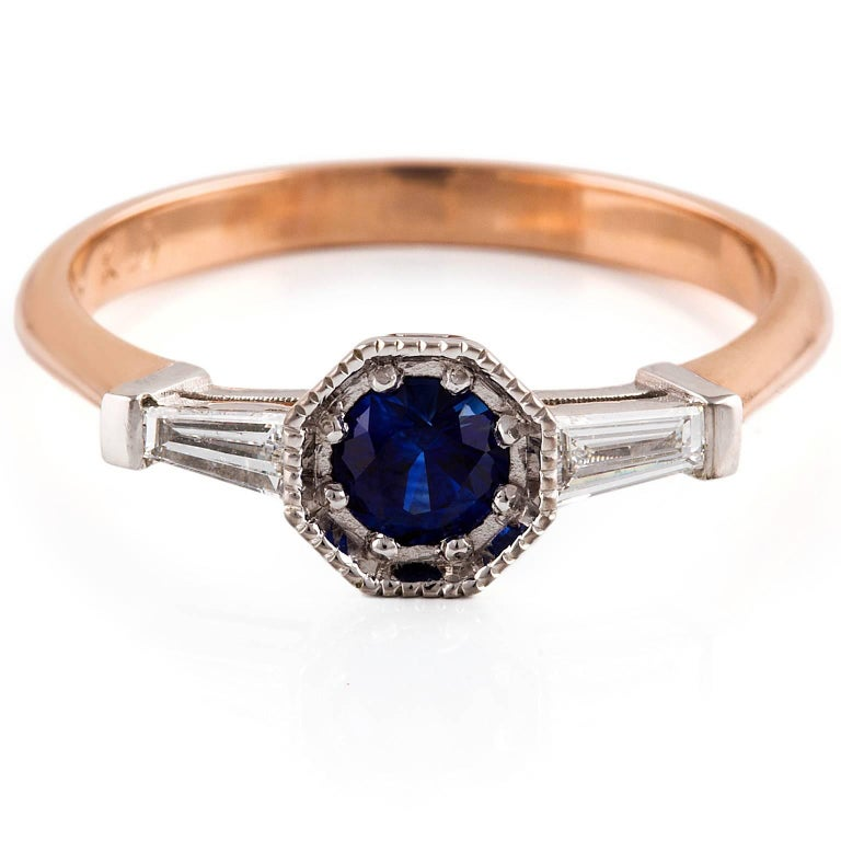Art Deco Dark Zaffiro Ring  With timeless appeal, this elegant Art Deco style ring is set with a stunning Ceylon Sapphire and tapered baguette diamonds. The white gold setting has lovely milgrain detailing and the band is made of rose gold.   1 x