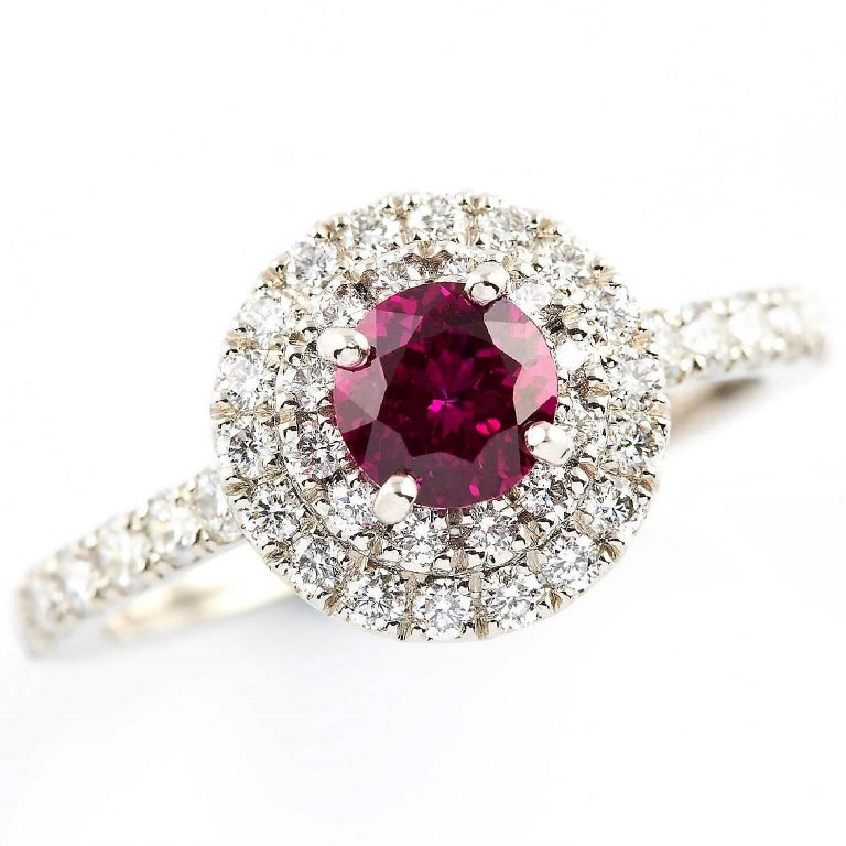 Rubino Halo Ring  This stunning platinum ring is set with an extraordinary round Burmese ruby complemented with a halo of diamonds. The diamonds are also set into the band. A distinctive heirloom piece.  Round faceted ruby: Deep bright pink, Burma