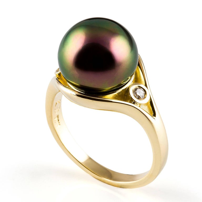 Tahitian Perla Ring  This statement ring in 18 carat yellow gold is set with a stunning Tahitian pearl. The band splits and sweeps around the pearl setting with a petite white diamond on either side.  Tahitian pearl: striking aubergine colour, high