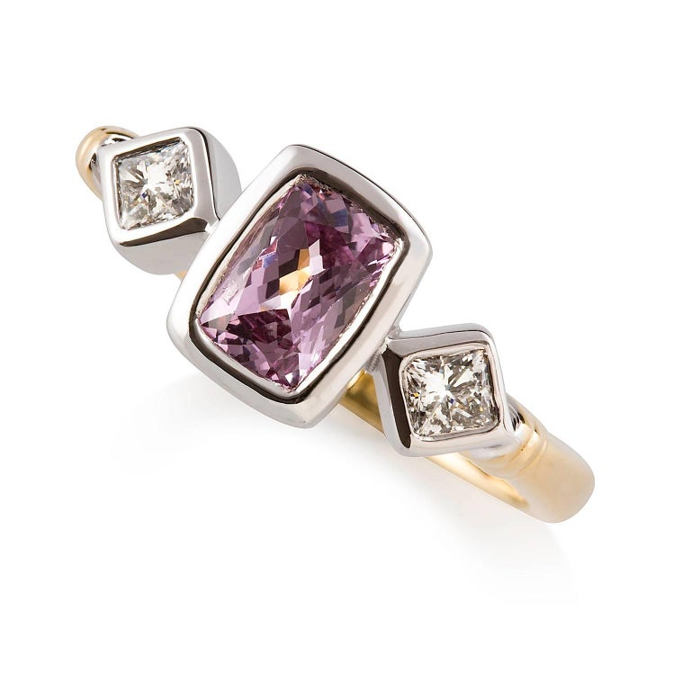 Rosa Zaffiro Ring  This gorgeous two-toned handmade dress ring features a stunning pink sapphire that is complimented with princess cut diamonds on either side, all set in 18ct white gold. The band is made of 18ct yellow gold with an understated