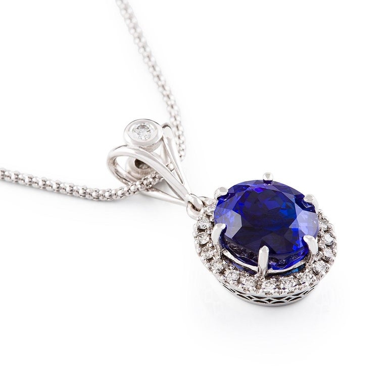 Tanzanite Halo Neckpiece  This absolutely stunning necklace features a finest blue tanzanite surrounded by a halo of diamonds. The fancy split bail has a chenier set diamond and is threaded upon the cable chain. Tanzanite is the birthstone of