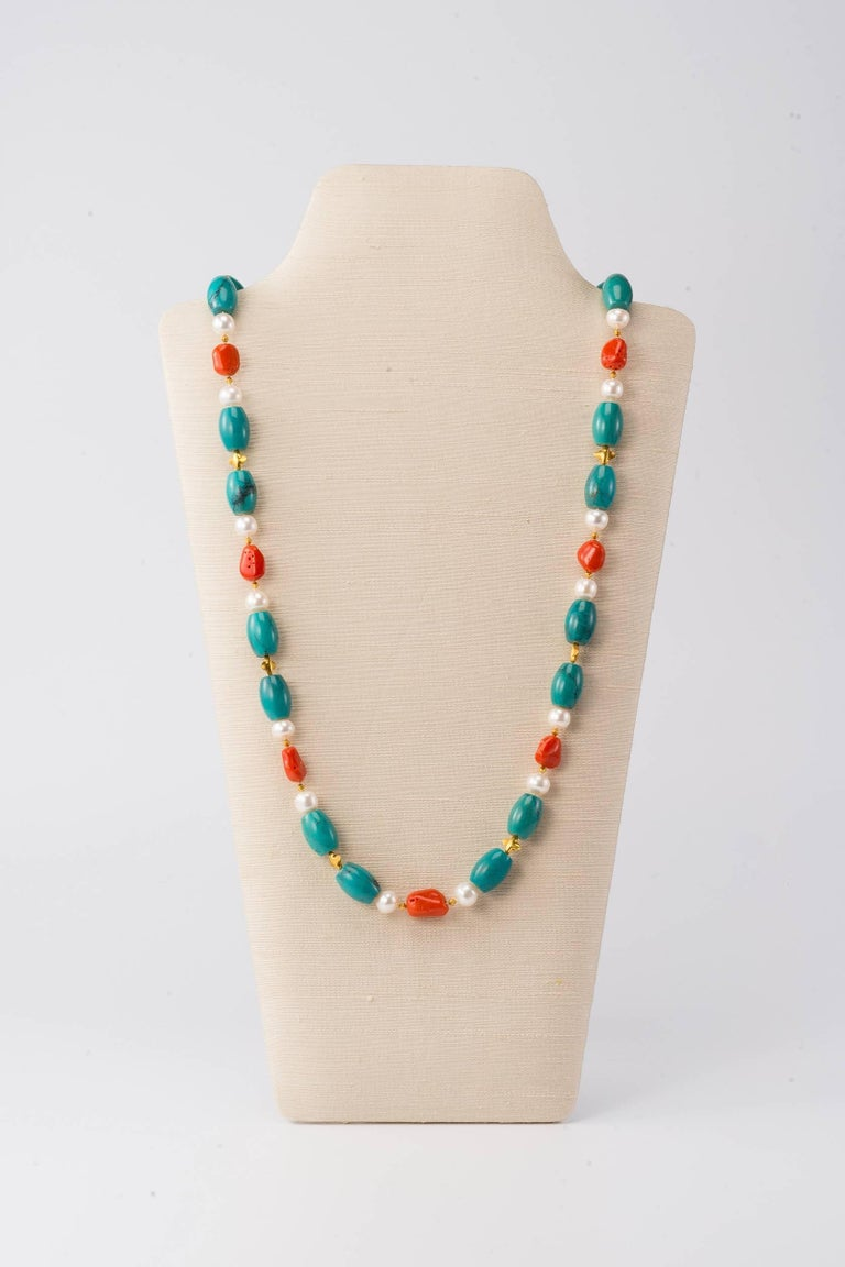 34 in (86.5cm) long necklace with Tibetan turquoise, Sardinian coral pebbles, freshwater pearls and 18K gold beads & clasp  This classic mix of turquoise, coral & pearls with gold bead accents can be worn long or twisted double around the