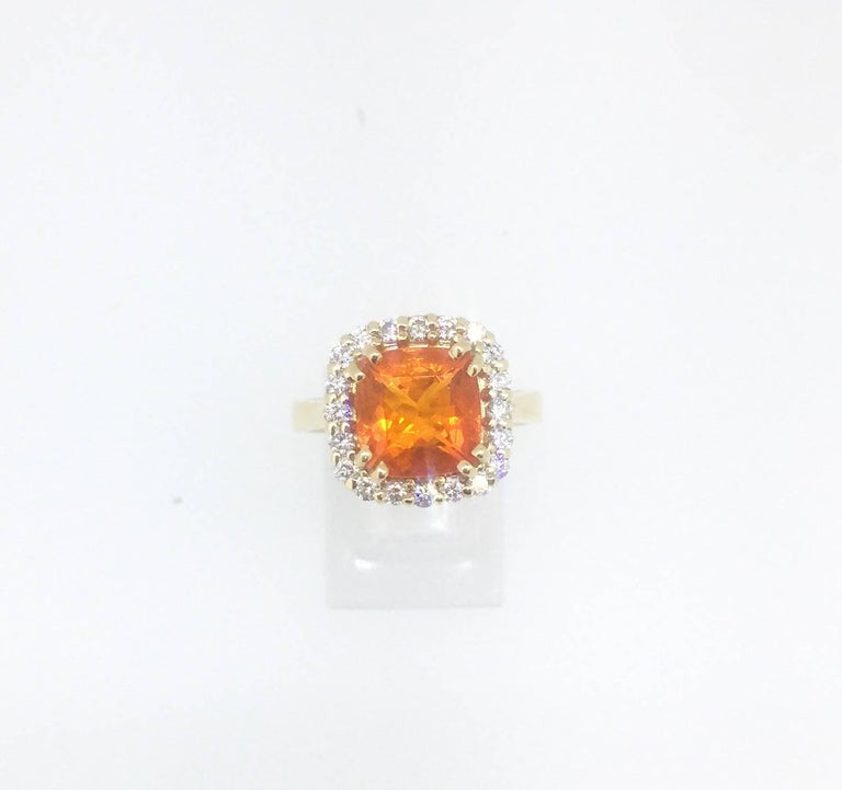 This ring has a 1.98 carat Fire Opal in the center of the ring and is surrounded by 20 Round Brilliant Cut Diamonds that weigh a total of 0.50 carat.  The Clarity is a VS and the Color is F.  The ring is a size 7 and can be re-sized if needed at no
