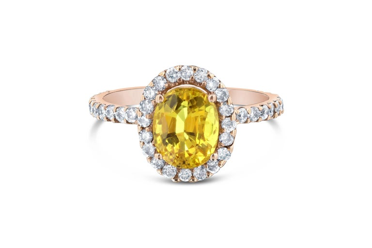 This ring has a 2.63 carat Oval Cut Yellow Sapphire in the center of the ring and is surrounded by a halo 44 Round Cut Diamonds that weigh 0.72 carats. The ring is casted in 14K Rose Gold and weighs approximately 3.1 grams.  This ring is a size 7