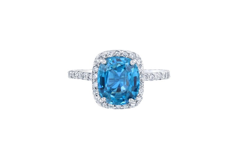 This beautiful halo ring has a 3.73 carat Blue Zircon set in the center of the ring. A Blue Zircon is a natural stone that is mined in Vietnam. The ring has a halo of 54 Round Brilliant Cut Diamonds that weigh 0.54 carats. (Clarity: VS - Color: I).