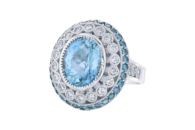 This ring has a 4.73 carat gorgeous Aquamarine set in the center of the ring and is surrounded by 24 Round Cut Diamonds that weigh 0.83 carat (Clarity: SI1, Color: F).  The ring also has 32 Round Cut Blue Diamonds that weigh 0.96 carat.   The total