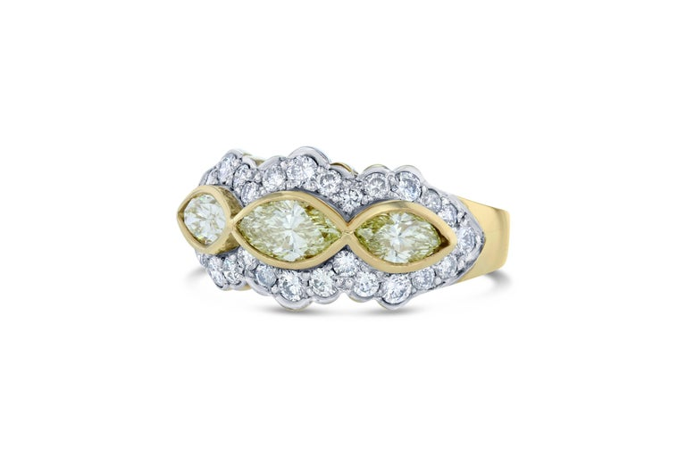 A gorgeous cocktail ring that will elevate your accessory collection !   There are 3 Natural Marquise cut Yellow Diamonds that weigh 0.97 carat and are surrounded by 28 Round cut diamonds that weigh 0.70 carat. The total carat weight of the ring is