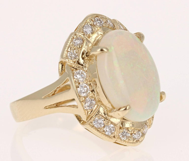 4.21 Carat Oval Cut Opal Diamond Yellow Gold Art Deco Ring!  Stunning Opal and Diamond Ring made in a 14K Yellow Gold setting.  The Oval Cut Opal in this ring weighs 3.65 carats and is surrounded by 20 Round Cut Diamonds that weigh 0.56 carat.  The