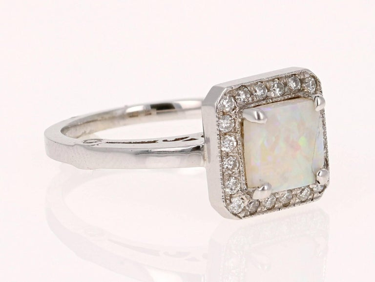 Cute Opal and Diamond Ring made in a 14K White Gold setting.  The Square Cut Opal in this ring weighs 0.99 carats and is surrounded by 24 Round Cut Diamonds that weigh 0.33 carat.  The total carat weight of this ring is 1.32 cts.  The ring is a size