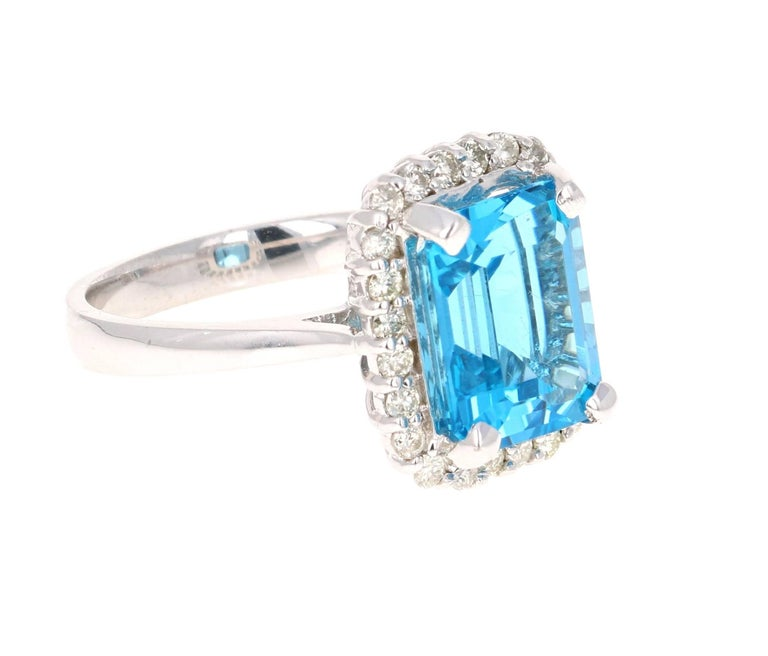 This beautiful Emerald Cut Blue Topaz and Diamond ring has a stunning 5.78 Carat Blue Topaz and its surrounded by 24 Round Cut Diamonds that weigh 0.44 Carats. The total carat weight of the ring is 6.22 Carats. The setting is crafted in 14K White