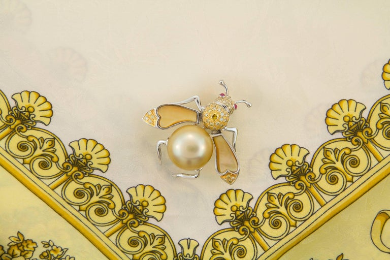 This golden pearl and fancy diamond bee brooch features a pearl of 17mm diameter. The flexible wings are set with custom cut synthetic yellow quartz. The design is complete with 0.90 carats of fancy color diamonds with ruby cabochon accents for