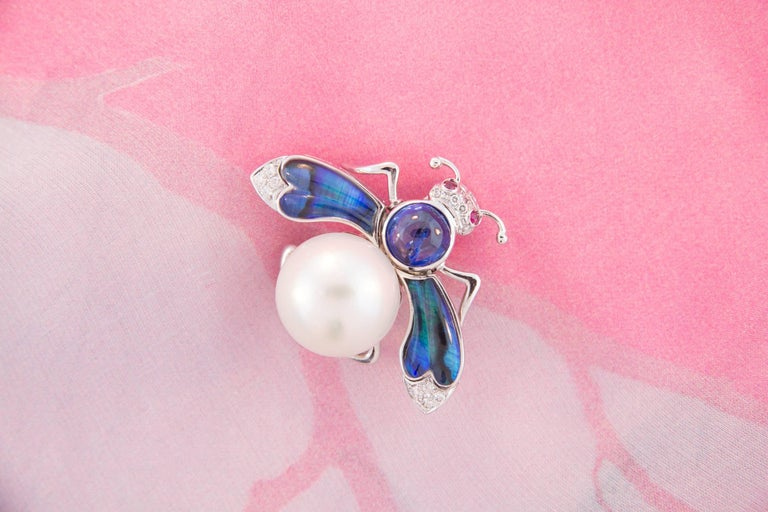 This South Sea pearl and diamond bee brooch features a pearl of 17.5mm diameter. The flexible wings are set with custom cut tinted paua shell topped by transparent crystal. The design is complete with a round cabochon blue Ceylon sapphire (3.34