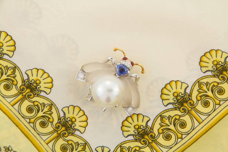This South Sea pearl and diamond bee brooch features a pearl of 17.5mm diameter. The wings are set with custom cut frosted crystal. The design is complete with a faceted drop shape blue Ceylon sapphire (0.95 carats) and 0.30 carats of round