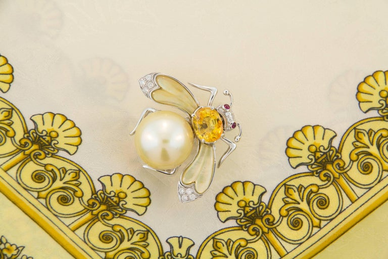 This golden pearl and diamond bee brooch features a pearl of 17.5mm diameter. The flexible wings are set with custom cut synthetic yellow quartz. The design is complete with an oval faceted yellow sapphire (4.10 carats) and 0.25 carats of round