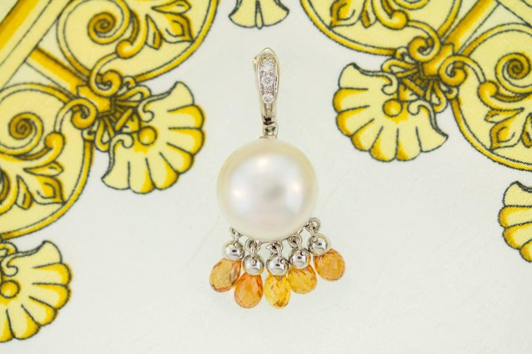 """This South Sea pearl pendant necklace features an Australian pearl of 13mm diameter suspending 5 orange briolette sapphires. It hangs from a hook set with diamonds and connects to a 21"""" 18 carat white gold chain decorated with 2 diamonds. The"""
