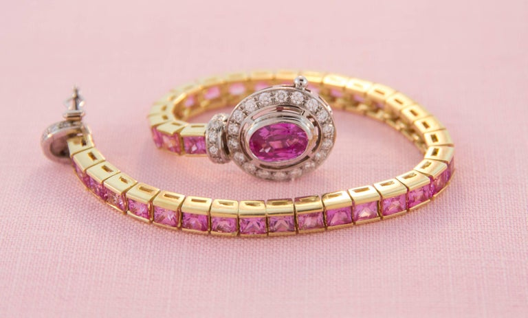 "The 6.5"" bracelet features a row of especially calibrated princess-cut pink sapphires (17.60 carats) flanked by a bridge set with round diamonds. The clasp consists of an oval shape faceted pink sapphire (1.66 carats) surrounded by diamonds. The"