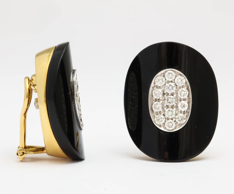 A pair of 18 karat yellow gold, diamond and onyx earclips. The total diamond weight is approximately 2 carats. Stamped 750 for 18 karat and an undistinguishable signature.  Posts can be added at no additional cost.