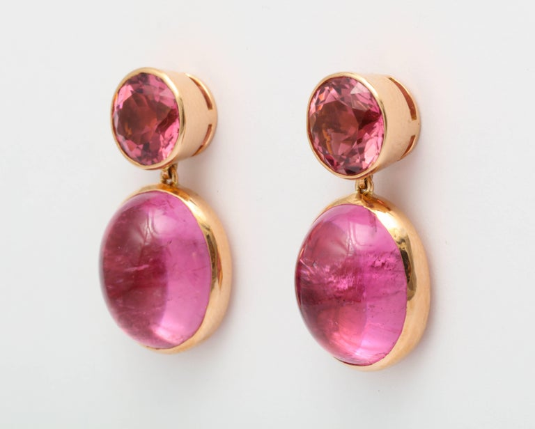 A pair of earrings set in 18 karat pink gold. Two round faceted pink tourmalines with a total weight of 5.68 carats. Two oval cabochon rubelites with a total weigh of 24.20 carats. Signed Donna Vock Designs.