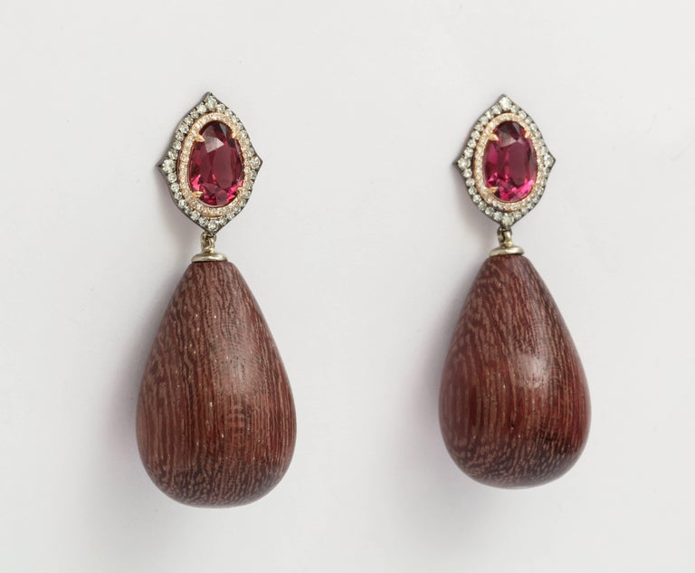 A pair of earrings featuring polished amaranth wood drops measuring 27 x 18mm. Set with 4.04 carats of rhodolite and 0.51 carats of diamonds in 18 karat gold. Friction backs.