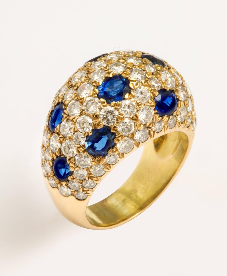 A super-stylish 18 karat yellow gold bombay ring pave set with round brilliant cut diamonds and oval sapphires. An estimated diamond weight of 4.00 carats and an estimated sapphire weight of 3.60 carats. Made in France with French marks. Circa