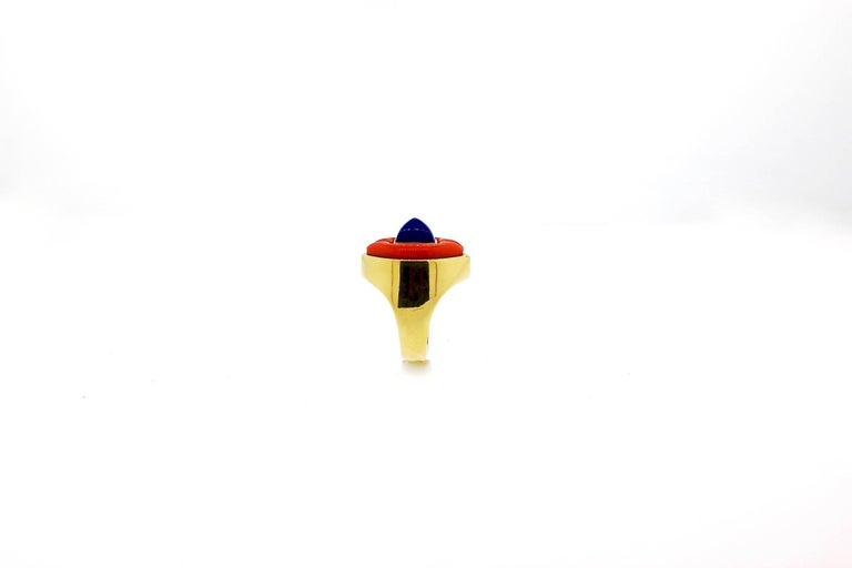 This is a handsome chic ring mixing two amazing stones - lapis and coral.  The coral is handcut to surround the sugarloaf lapis.  The dome ring is made in 18k gold.  It creates a color vintage look that mixes well with gold chains, pendants and